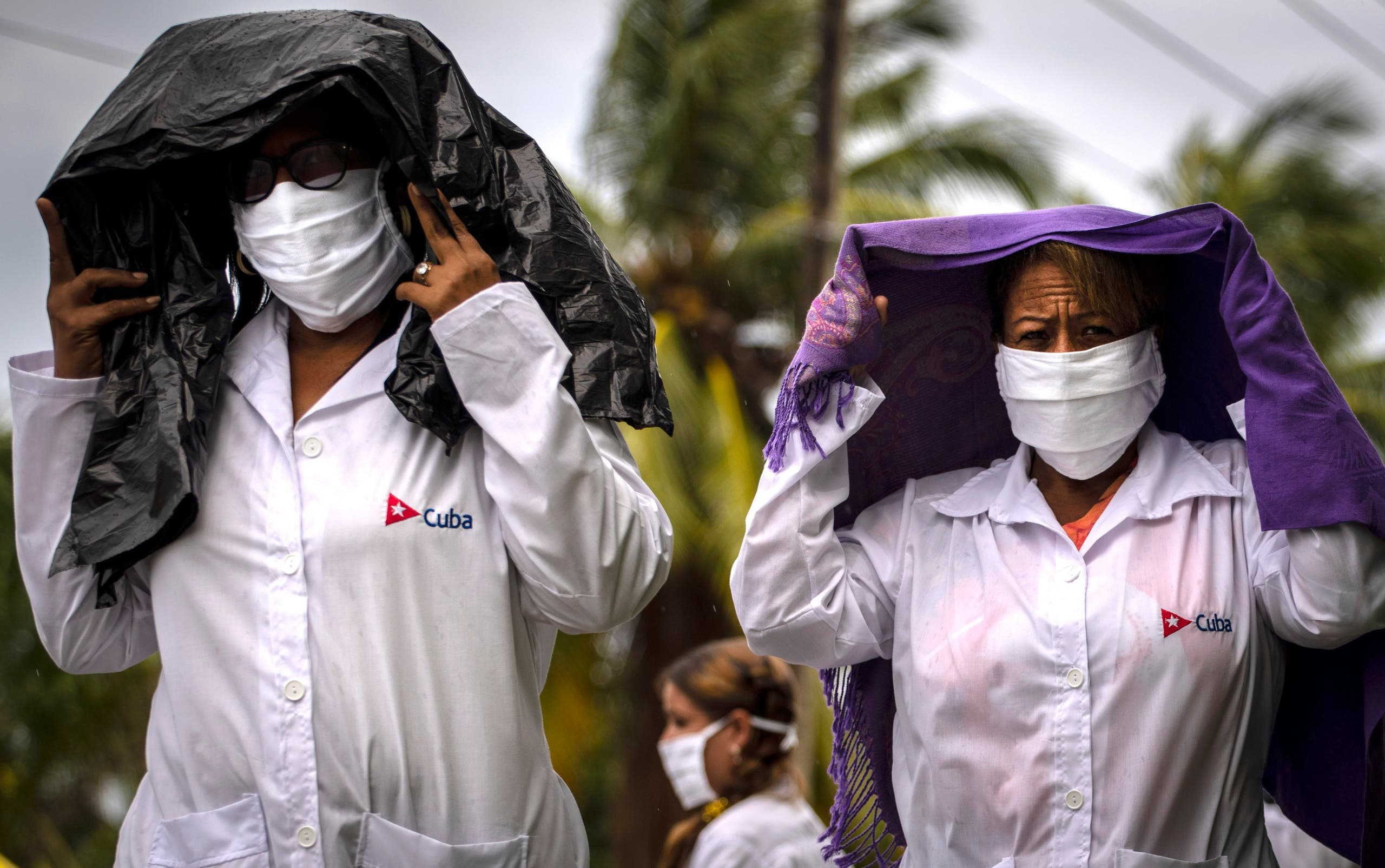 Health professionals who volunteered to travel to Kuwait to treat of coronavirus patients walk in the rain after attending their farewell ceremony in Havana, Cuba, Thursday, June 4, 2020. (AP)