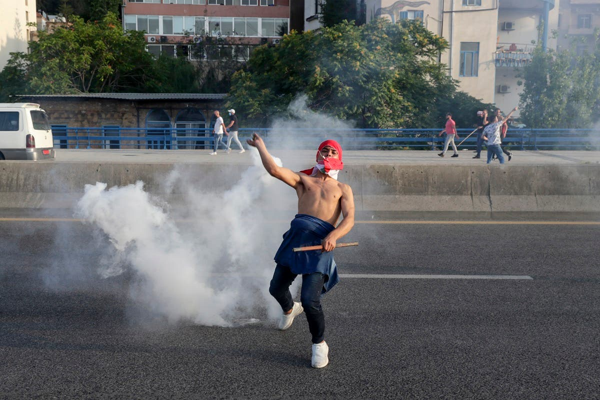 A Lebanese protester gestures amid clashes with riot police following a demonstration in central Beirut on June 6, 2020. (AFP)