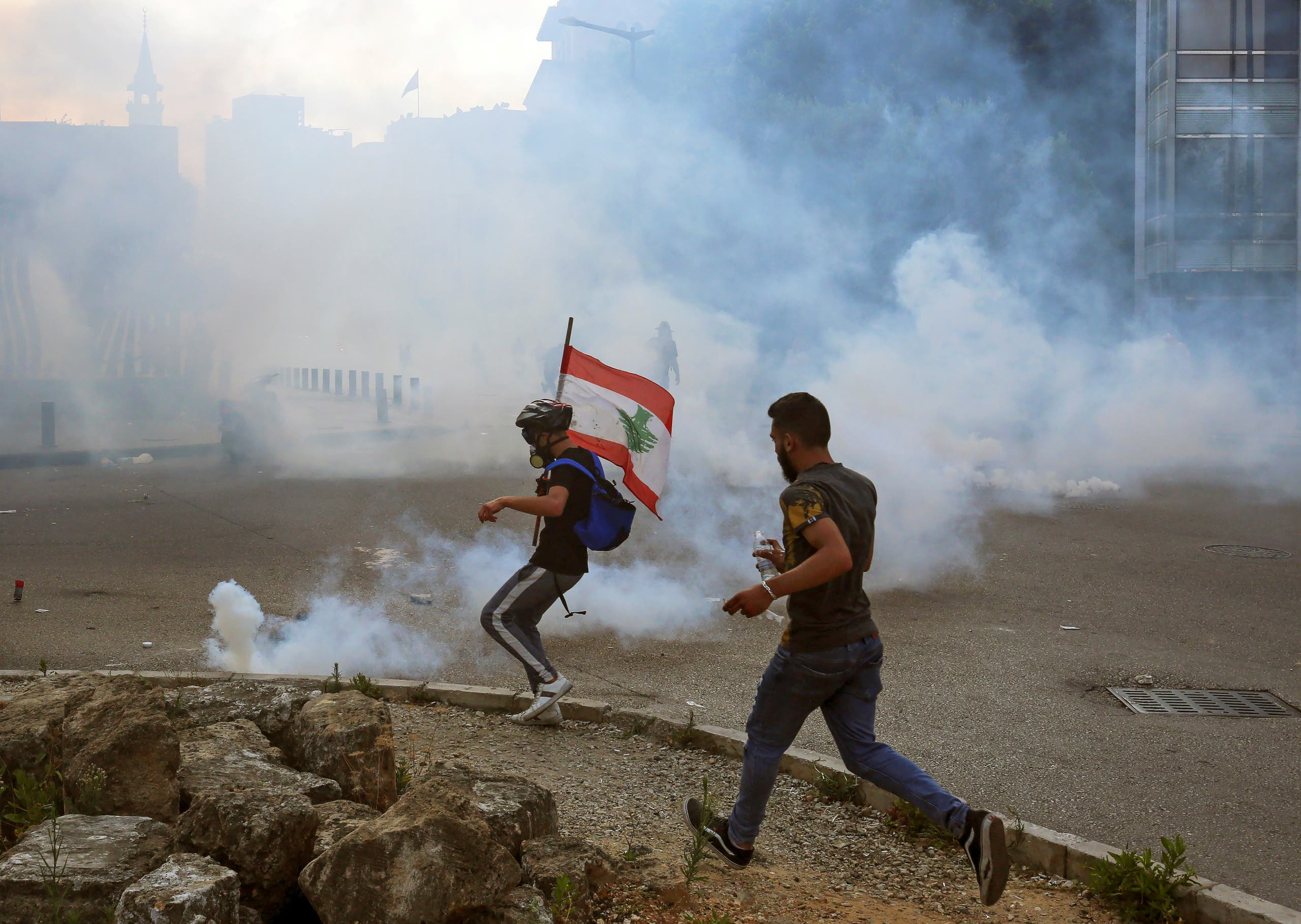 Demonstrators run amid a cloud of tear gas during a protest against the government performance and worsening economic conditions, in Beirut, Lebanon June 6, 2020. (Reuters)