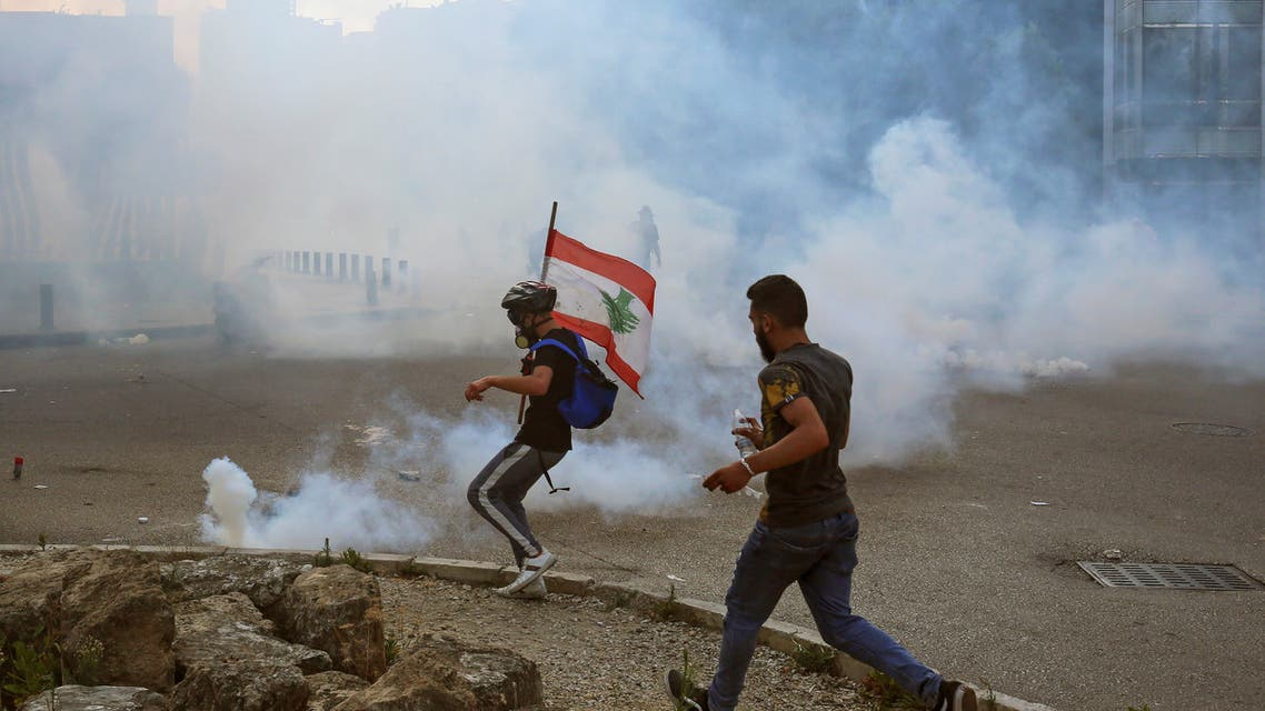Demonstrators run amid a cloud of tear gas during a protest against the government performance and worsening economic conditions, in Beirut, Lebanon June 6, 2020. REUTERS/Aziz Taher