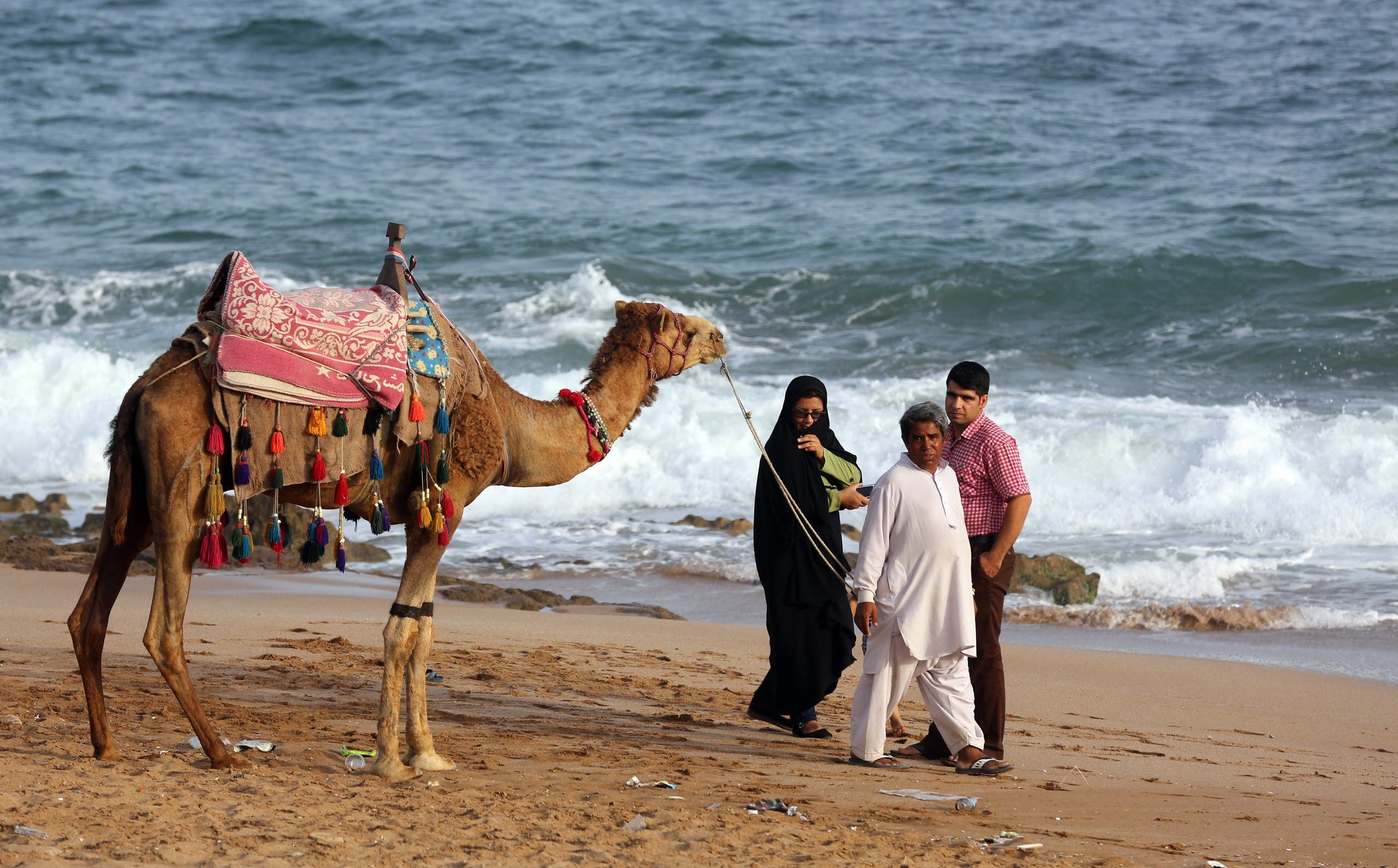 An Iranian family prepare to ride a camel on the beach in the southern Iranian coastal city of Chabahar on May 11, 2015. (File photo: AP)