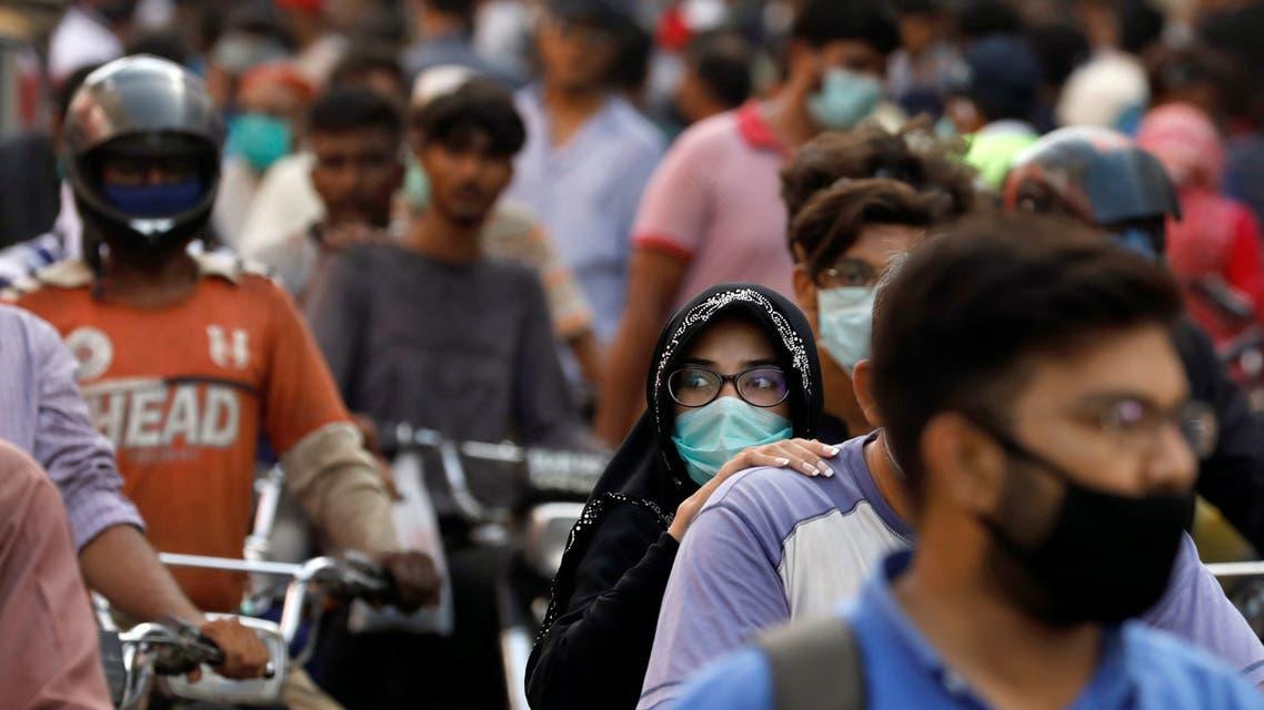 People wear face masks outside a market in Karachi, Pakistan. (File photo: Reuters)