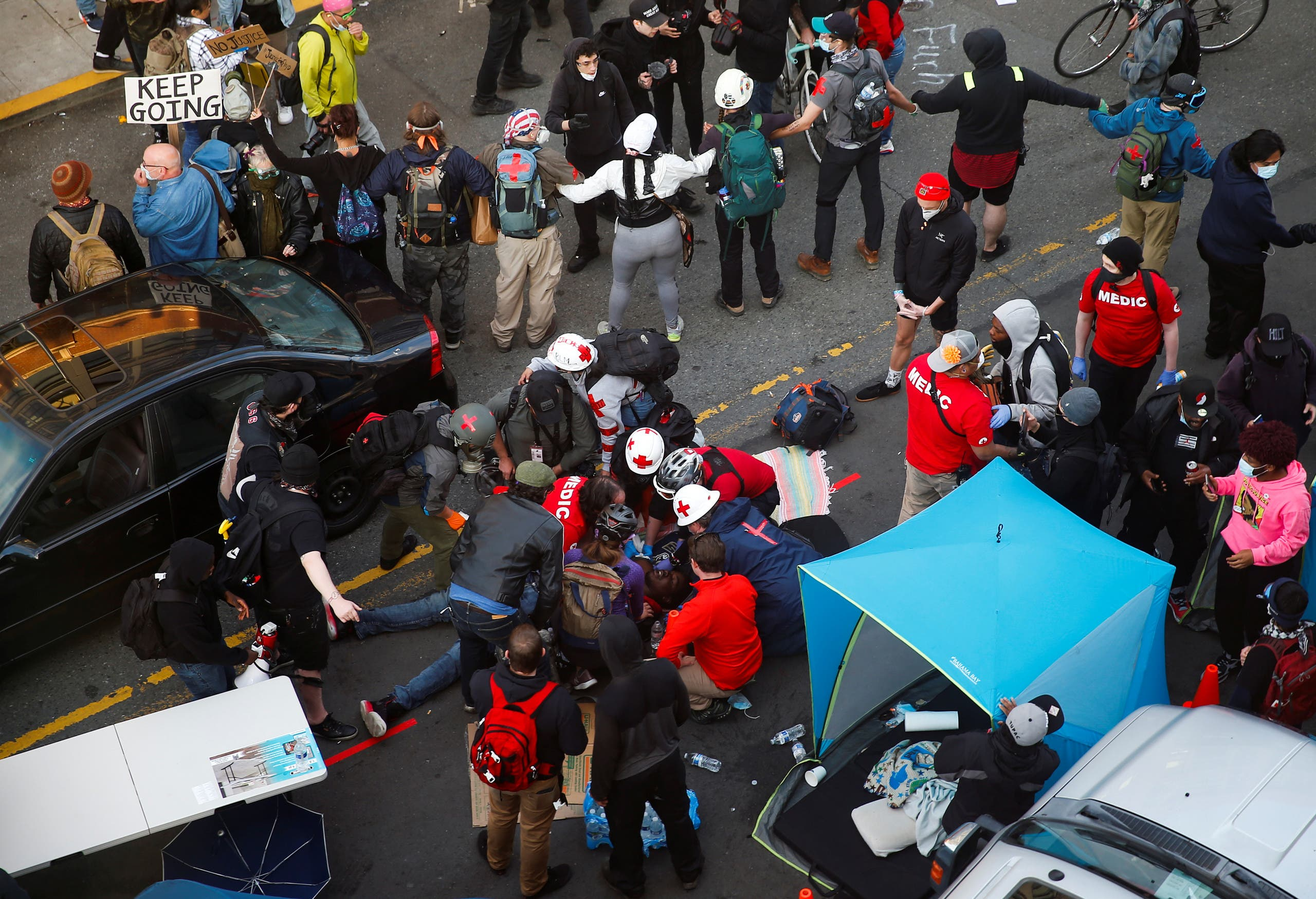 Paramedics attend to an injured person at the scene after a man drove a car into a crowd in Seattle, June 7, 2020. (Reuters)