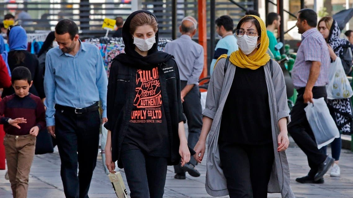 Iranians, some wearing face masks, walk along a street in the capital Tehran on June 3, 2020, amid the novel coronavirus pandemic crisis. (AFP)