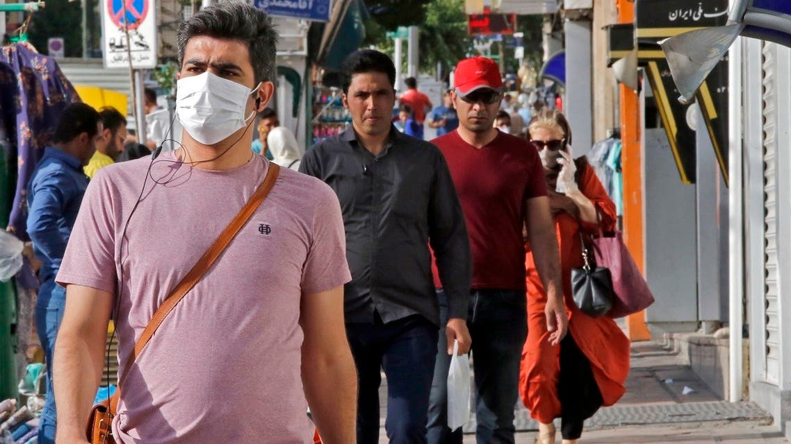 Iranians, some wearing face masks, walk along a street in the capital Tehran on June 3, 2020. (AFP)