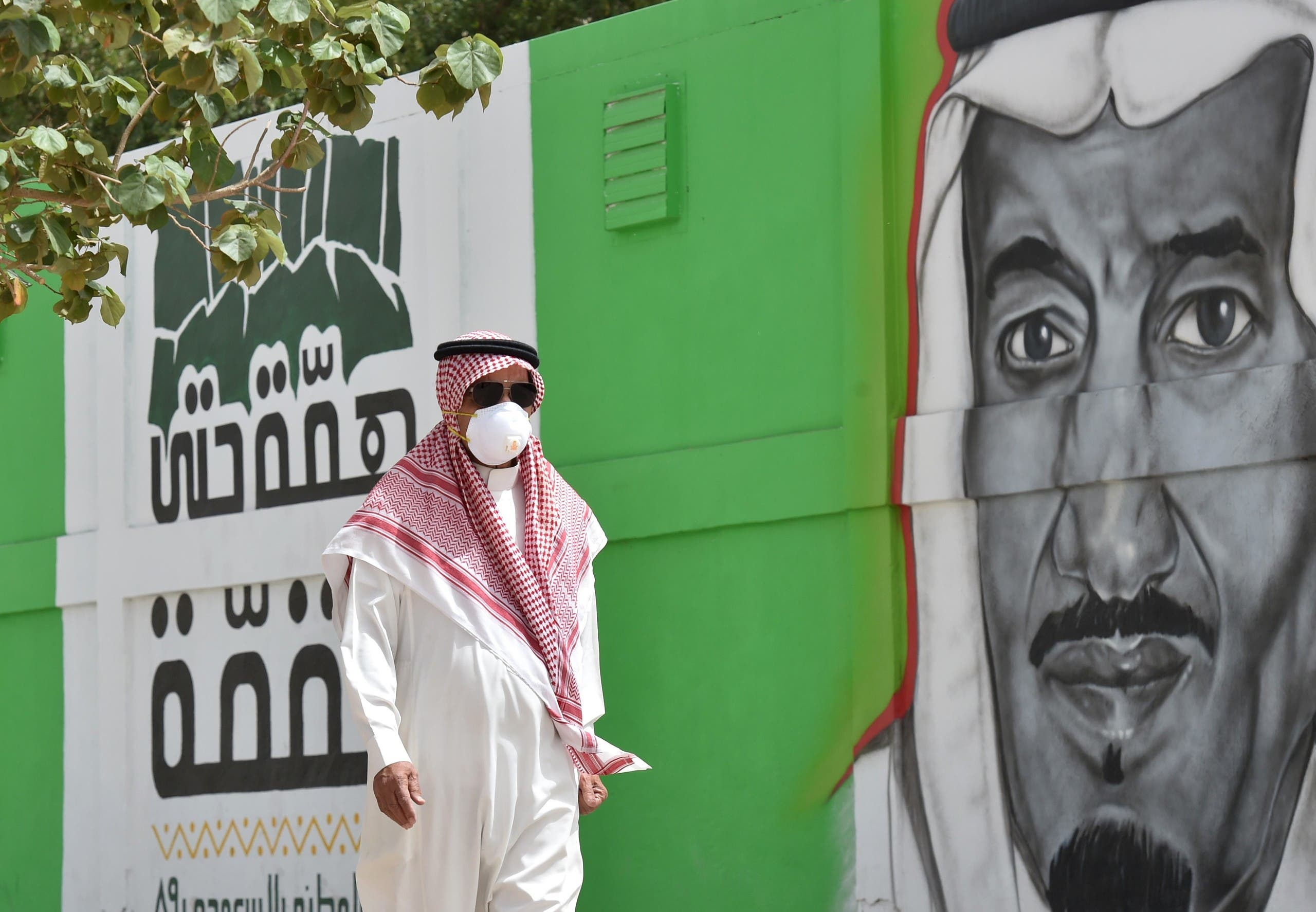 A Saudi man walks past a mural showing the face of King Salman bin Abdulaziz, in Riyadh on March 15, 2020. (AFP)