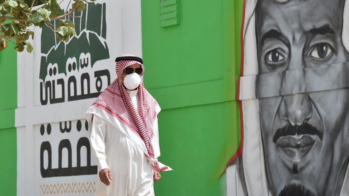 A Saudi man walks past a mural showing the face of King Salman bin Abdulaziz, in Riyadh on March 15, 2020. (AFP)