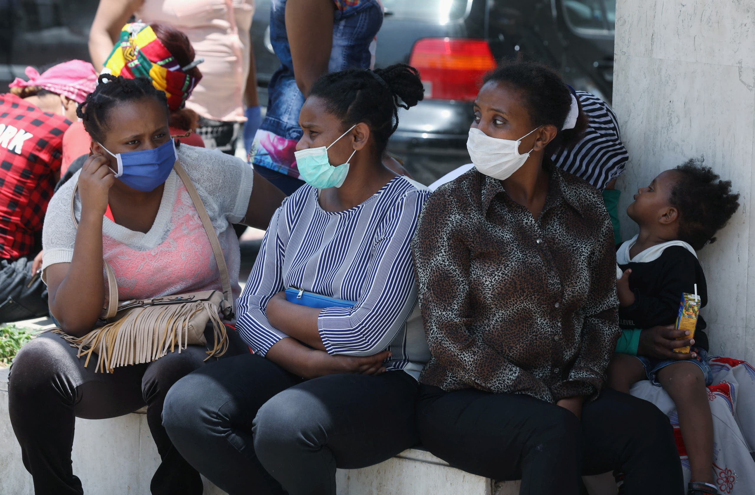 Ethiopian domestic workers wearing masks sit together with their belongings in front of the Ethiopian consulate in Hazmiyeh, Lebanon, June 8, 2020. (Reuters)