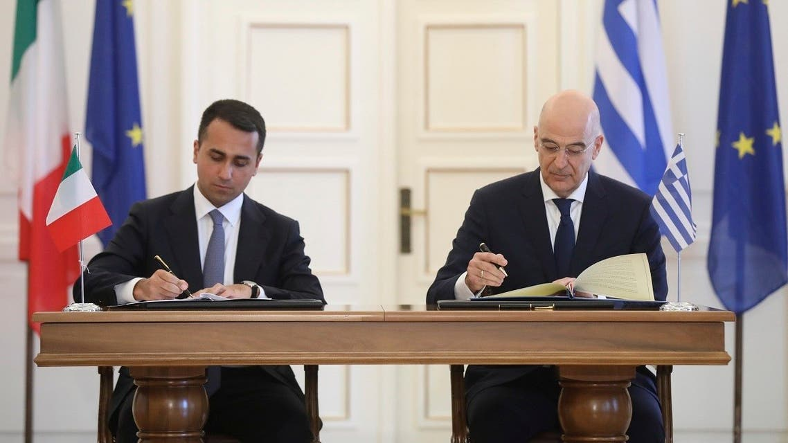 Greek Foreign Minister Nikos Dendias, right, and his Italian counterpart Luigi Di Maio asign an agreement following their meeting , in Athens, on Tuesday, June 9, 2020. (AP)