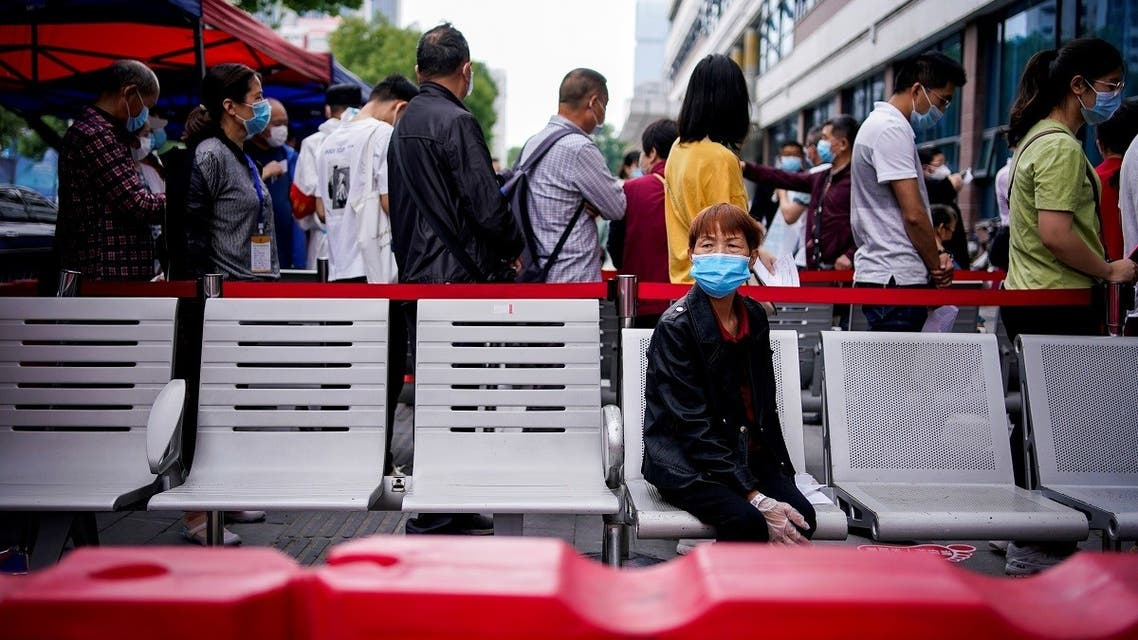 File picture of a woman wearing a face mask looking on in front of others standing in a queue for nucleic acid testings in Wuhan. (Reuters)
