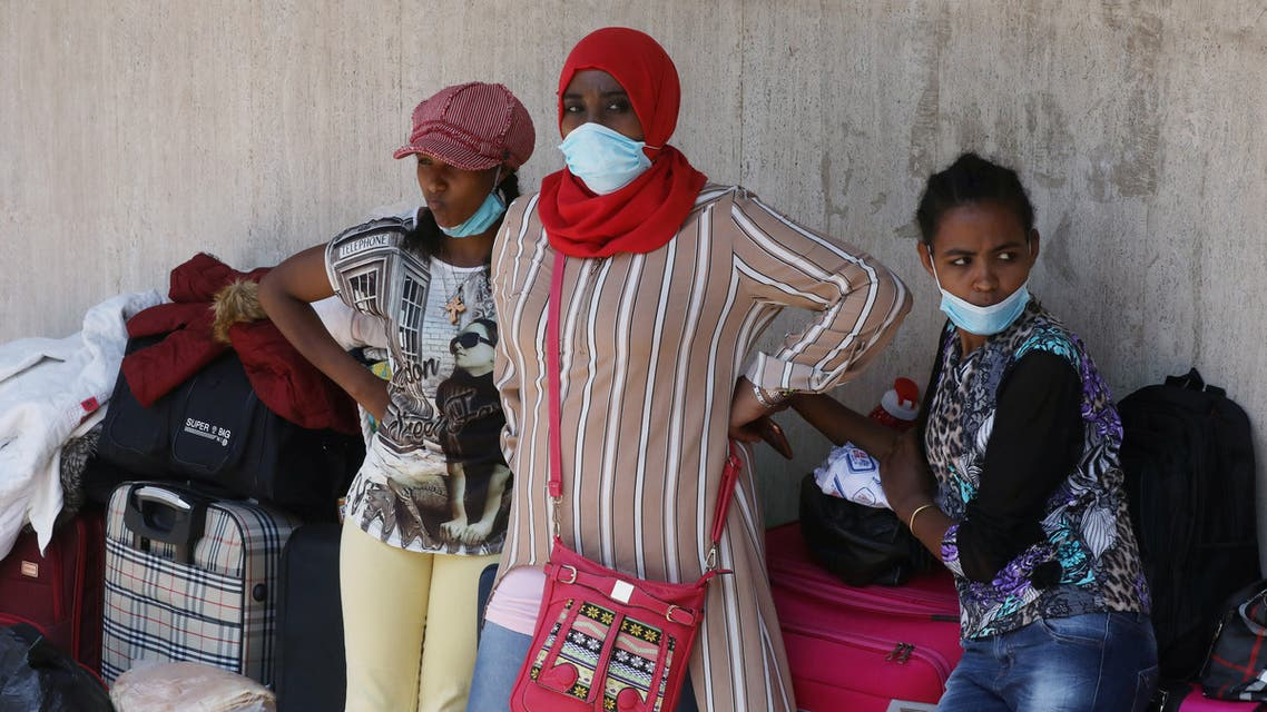 Ethiopian domestic workers wearing masks gather with belongings in front of the Ethiopian consulate in Hazmiyeh, Lebanon, June 8, 2020. (Reuters)