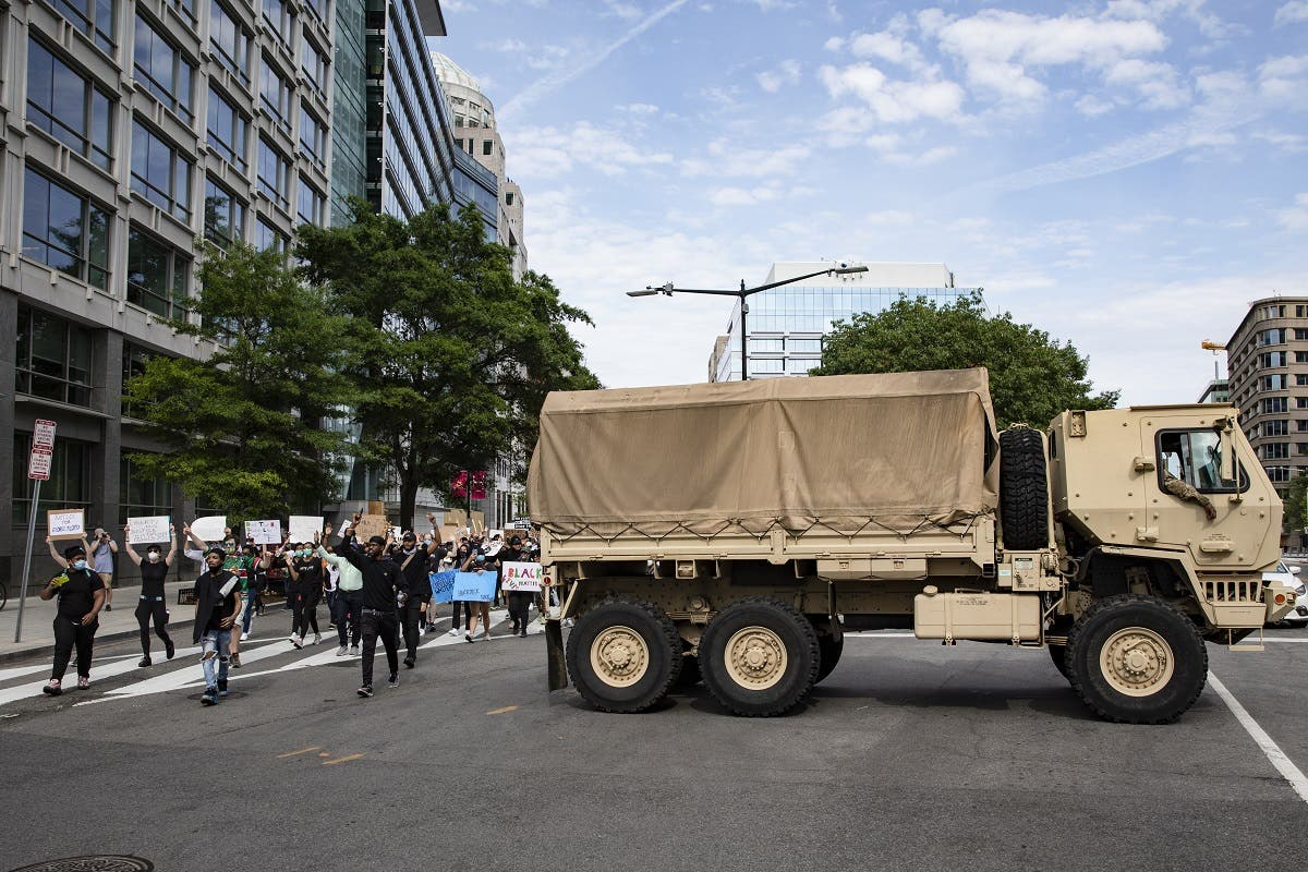 Protesters march past DC National Guard troops during demonstrations over the death of George Floyd, on June 2, 2020 in Washington, DC. (AFP)