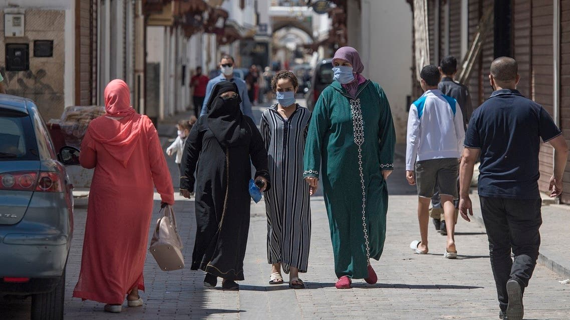 Pedestrians, wearing protective masks due to the COVID-19 pandemic, walk past closed shops in the Moroccan capital Rabat on June 10, 2020, as the government declared the extension of coronavirus lockdown until July 10. (AFP)