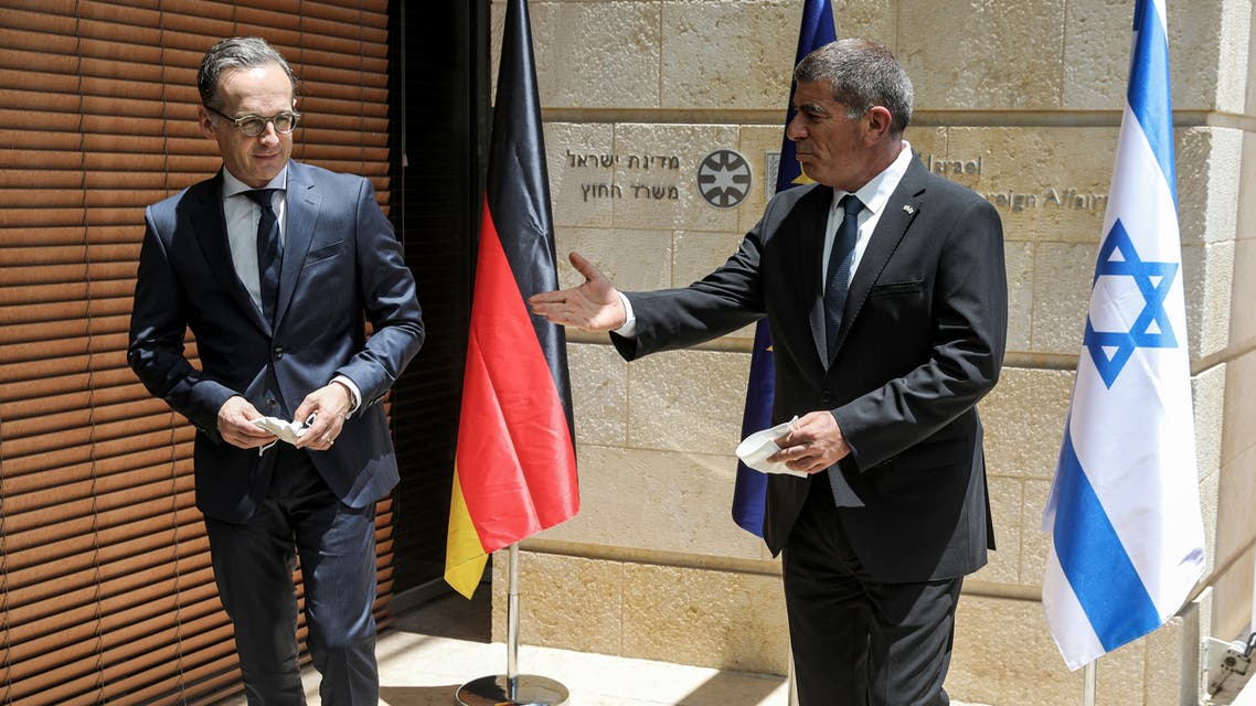 German Foreign Minister Heiko Maas and his Israeli counterpart Gabi Ashkenazi hand each other documents during their news conference in Jerusalem June 10, 2020. REUTERS/Ronen Zvulun