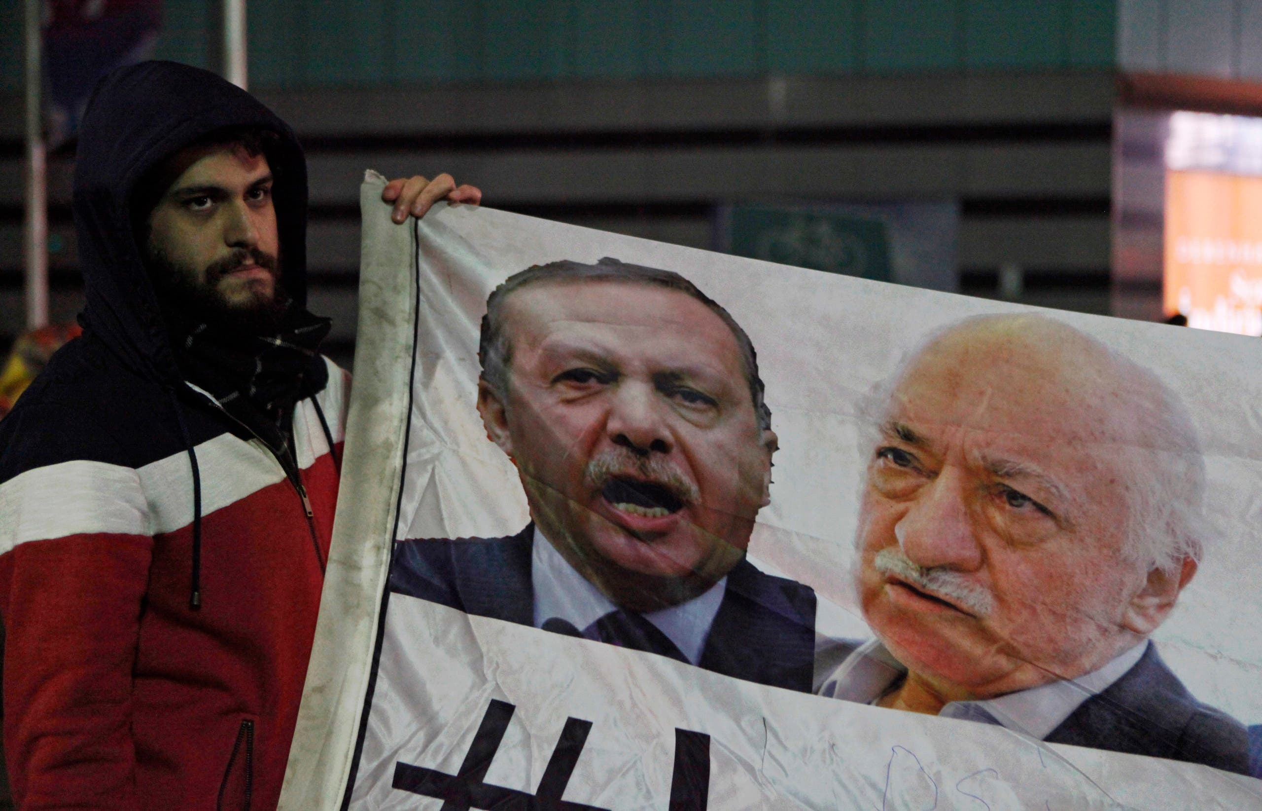 A demonstrator hold pictures of Turkey's Prime Minister Tayyip Erdogan and Turkish cleric Fethullah Gulen (R), in Istanbul December 30, 2013. (Reuters)