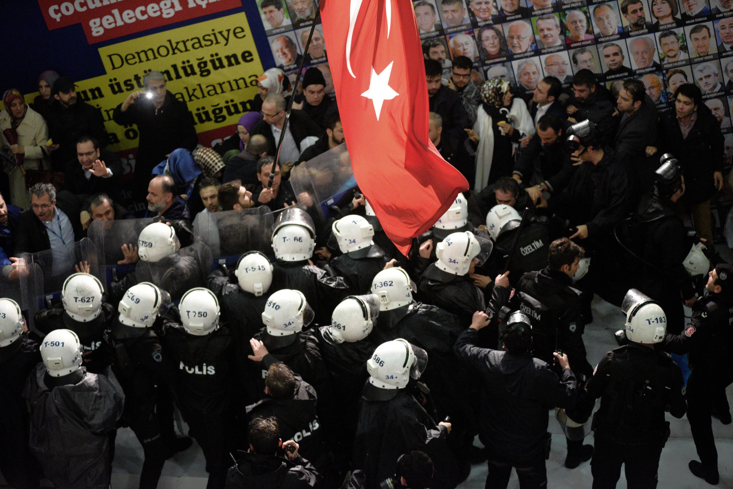 Riot police enter the headquarters of Zaman newspaper after using teargas and water cannons against the people gathered outside in support, in Istanbul on March 4, 2016. (AP)