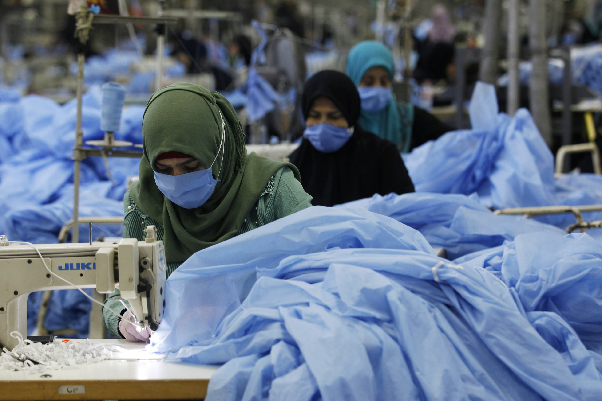 Women sew protective suits, following the outbreak of the coronavirus disease (COVID-19), at a factory in the holy city of Najaf, Iraq June 10, 2020. (Reuters)