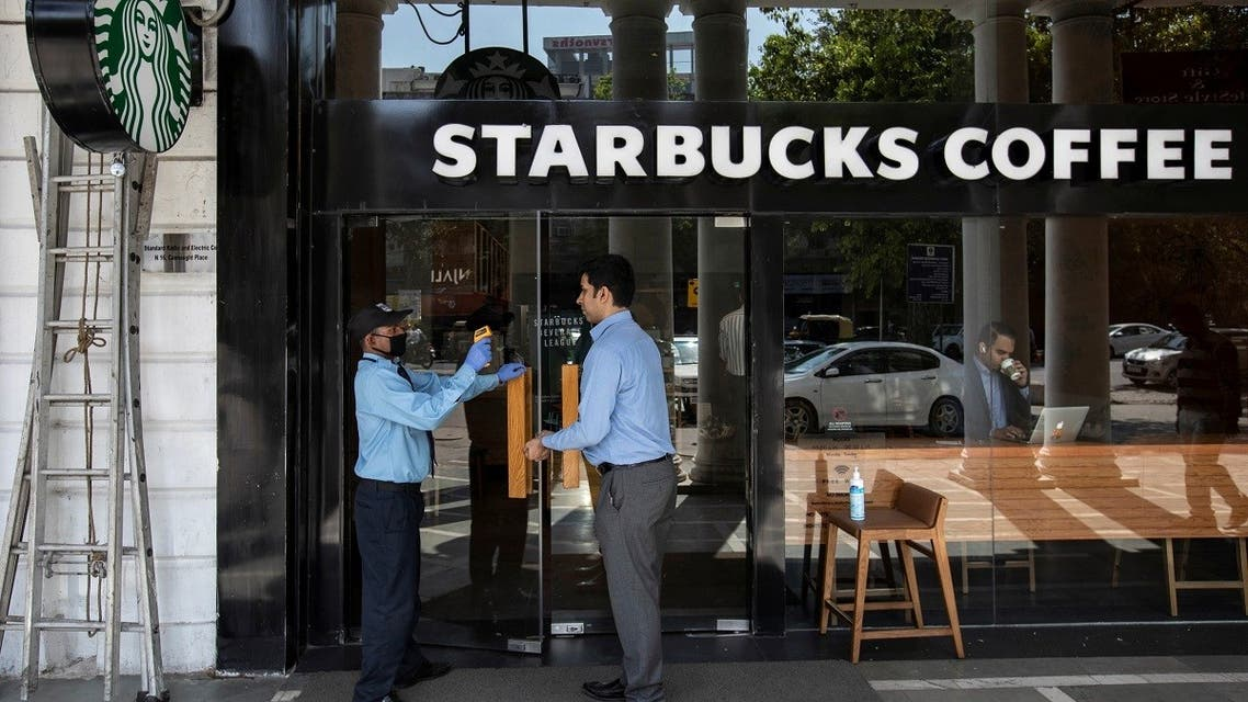 A private security guard checks the body temperature of a customer outside a Starbucks coffee shop, as a precaution against the spread of coronavirus, in New Delhi. (Reuters)