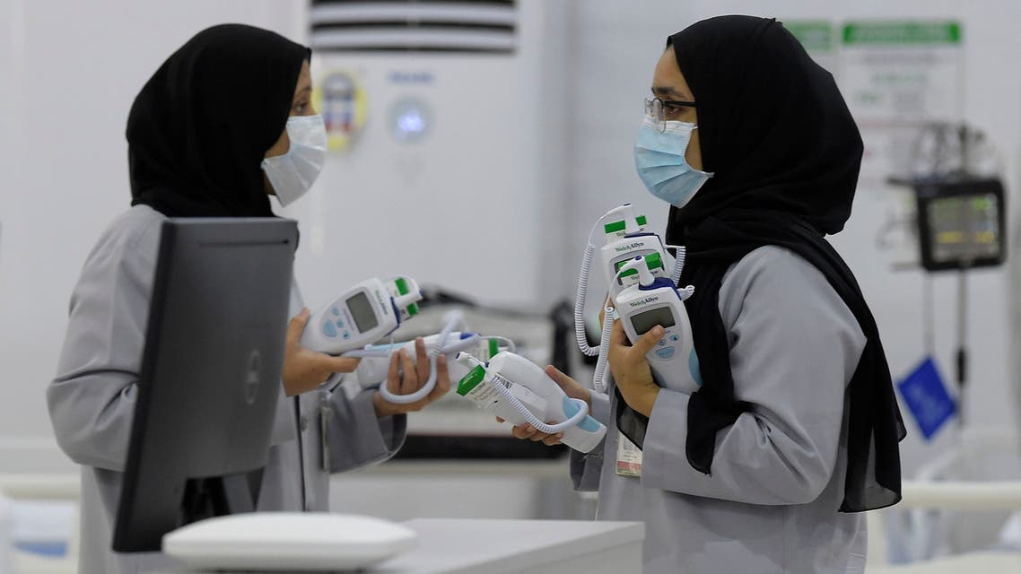 Bahraini health workers are pictured at the Sitra field Intensive Care Unit (ICU) hospital for COVID-19 patients, on May 4, 2020 in Sitra island south of the Bahraini capital Manama. The hospital, which is attached to a quarantine camp and spread-out over an area of 2400 square meters, is the first field Intensive Care Unit (ICU) to be setup far from a hospital and has its own lab, pharmacy, medical supply store, X-ray machines, and mobile dialysis units. It is run by 55 doctors and 250 nurses. It is the second field hospital out of five planned to add 500 ICU beds to Bahrain's health network.
