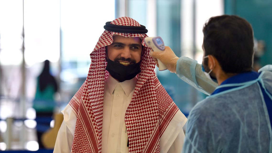 A Saudi health worker takes the temperature of a passenger at terminal 5 in the King Fahad International Airport, designated for domestic flights, in the capital Riyadh on May 31, 2020, after authorities lifted the ban on flights within the country.