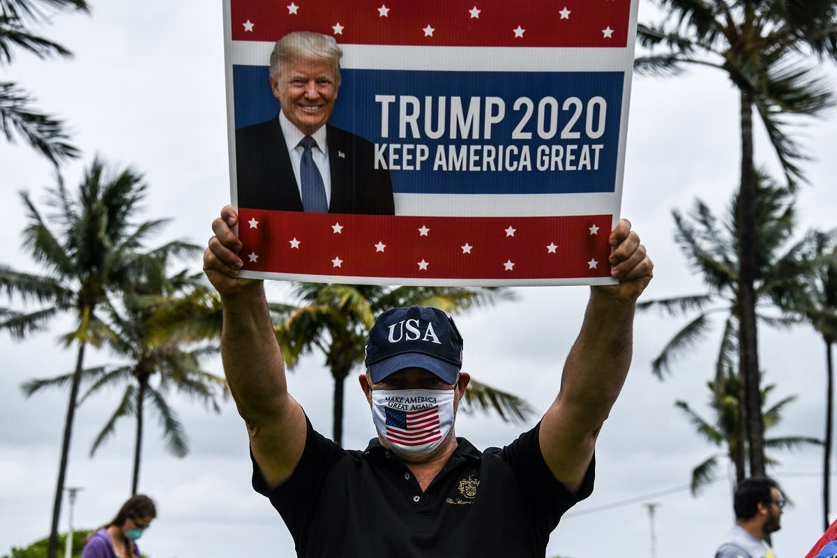 A supporter of US President Donald Trump holds an election poster as he participates in a Freedom Rally protest in support of opening Florida in South Beach in Miami, on May 10, 2020. (File photo: AFP)