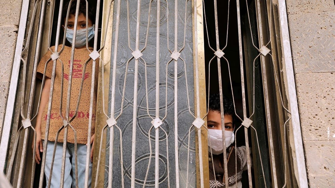 Children wearing protective masks look from behind a window during a 24-hour curfew amid concerns about the spread of the coronavirus disease (COVID-19), in Sanaa. (File photo: Reuters)