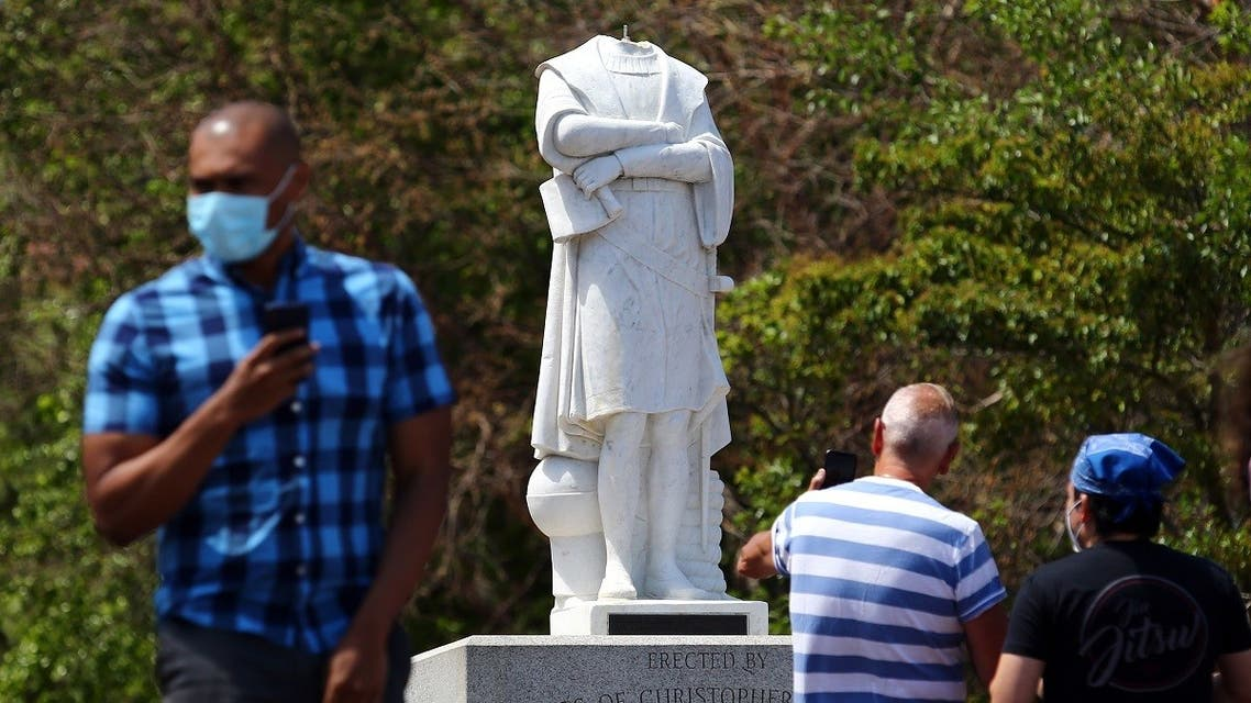 People photograph a statue depicting Christopher Columbus which had its head removed at Christopher Columbus Waterfront Park on June 10, 2020 in Boston, Massachusetts. (AFP)