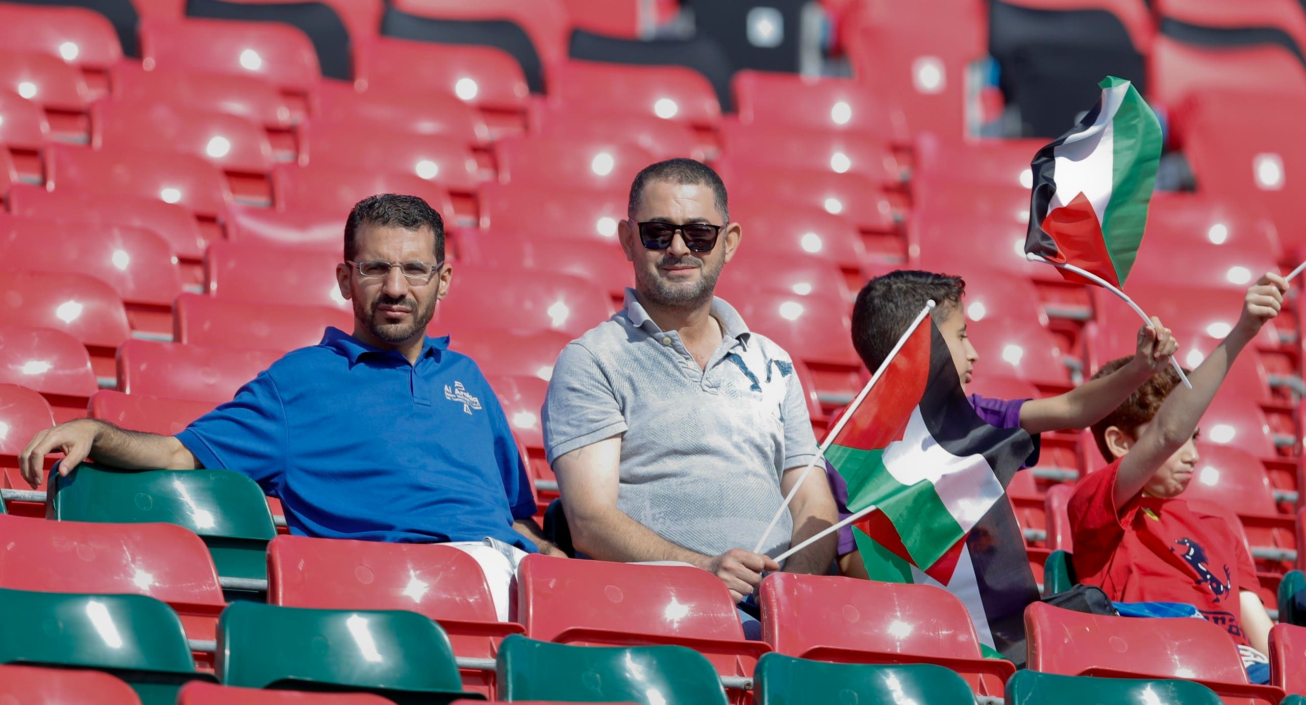 Supporters hold Palestinian flags as they sit in the stands prior to the AFC Asian Cup group B soccer match between Australia and Palestine at Al Maktoum Stadium in Dubai, United Arab Emirates on Jan. 11, 2019. (AP)