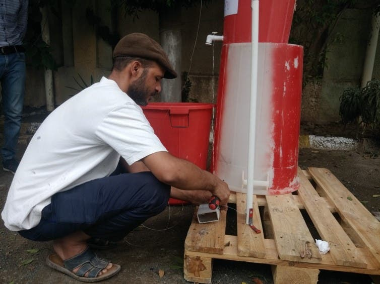MSF handyman, Adeel, constructs a foot-operated handwashing point in MSF's hospital in Taiz Houban, May 2020. (MSF)