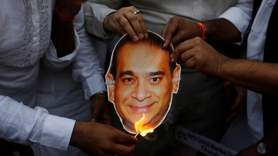 Activists of the youth wing of India's main opposition Congress party burn a cut-out with an image of billionaire jeweller Nirav Modi during a protest in Mumbai. (Reuters)