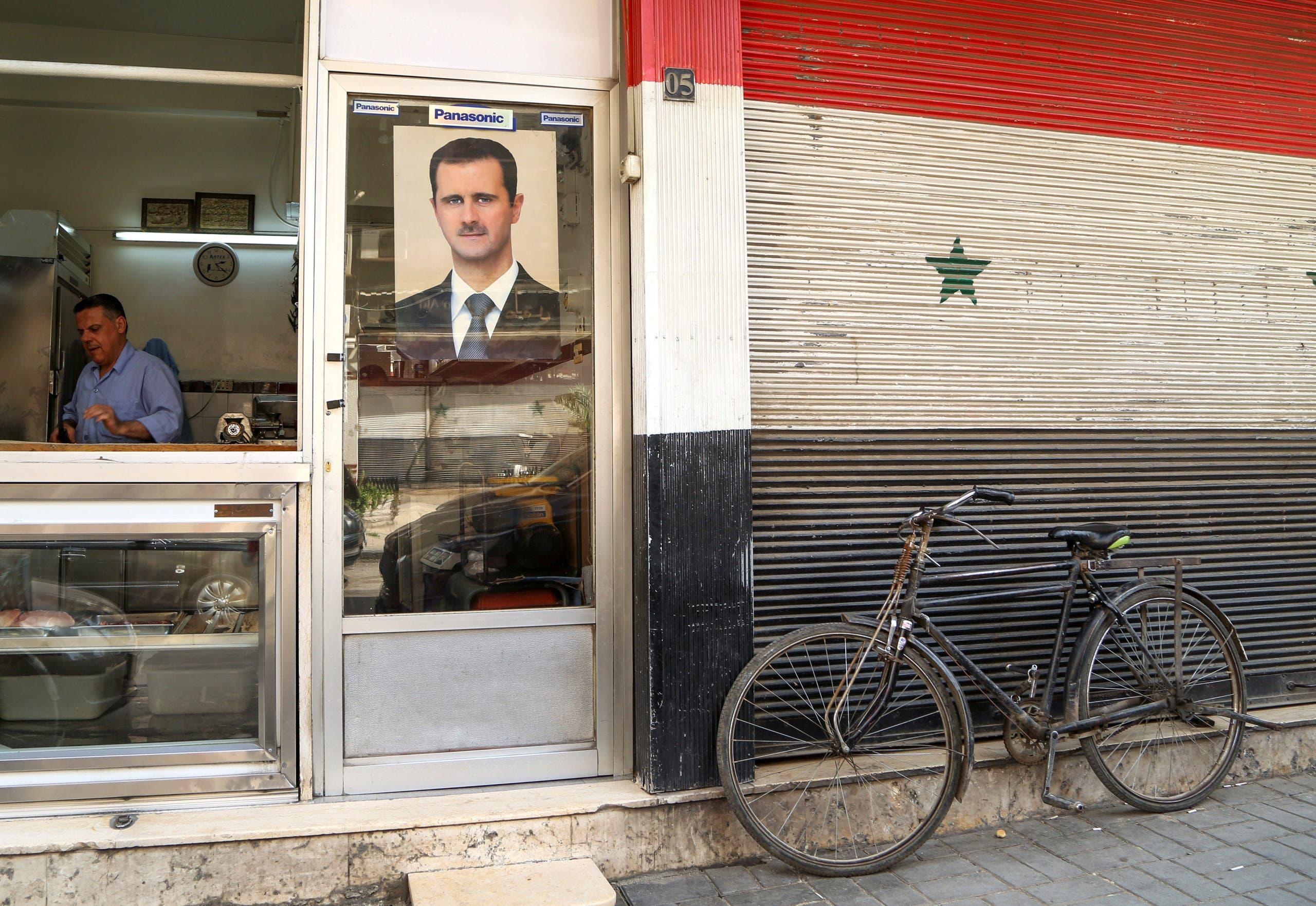 صورة بشار الأسد  على واجهة أحد المحال في دمشق (أرشيفية- رويترز)