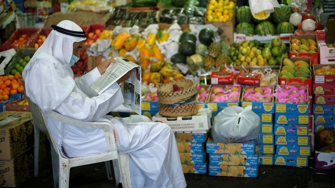 A Bahraini vendor, wearing a face mask, following the outbreak of the coronavirus disease (COVID-19), reads a newspaper as he waits for customers at his fruits stand, in Central Market, in Manama, Bahrain, June 13, 2020. (Reuters)