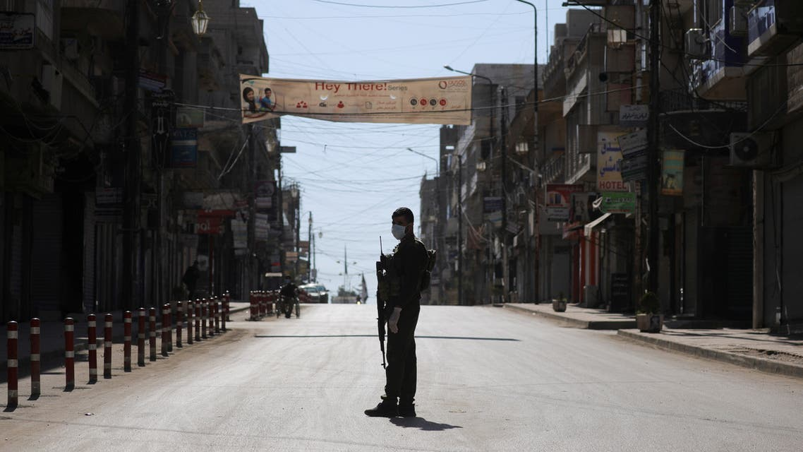 A member of the Asayish stands near closed shops along an empty street, as restrictions are imposed as measure to prevent the spread of the coronavirus disease (COVID-19) in Qamishli, Syria March 23, 2020. REUTERS/Rodi Said