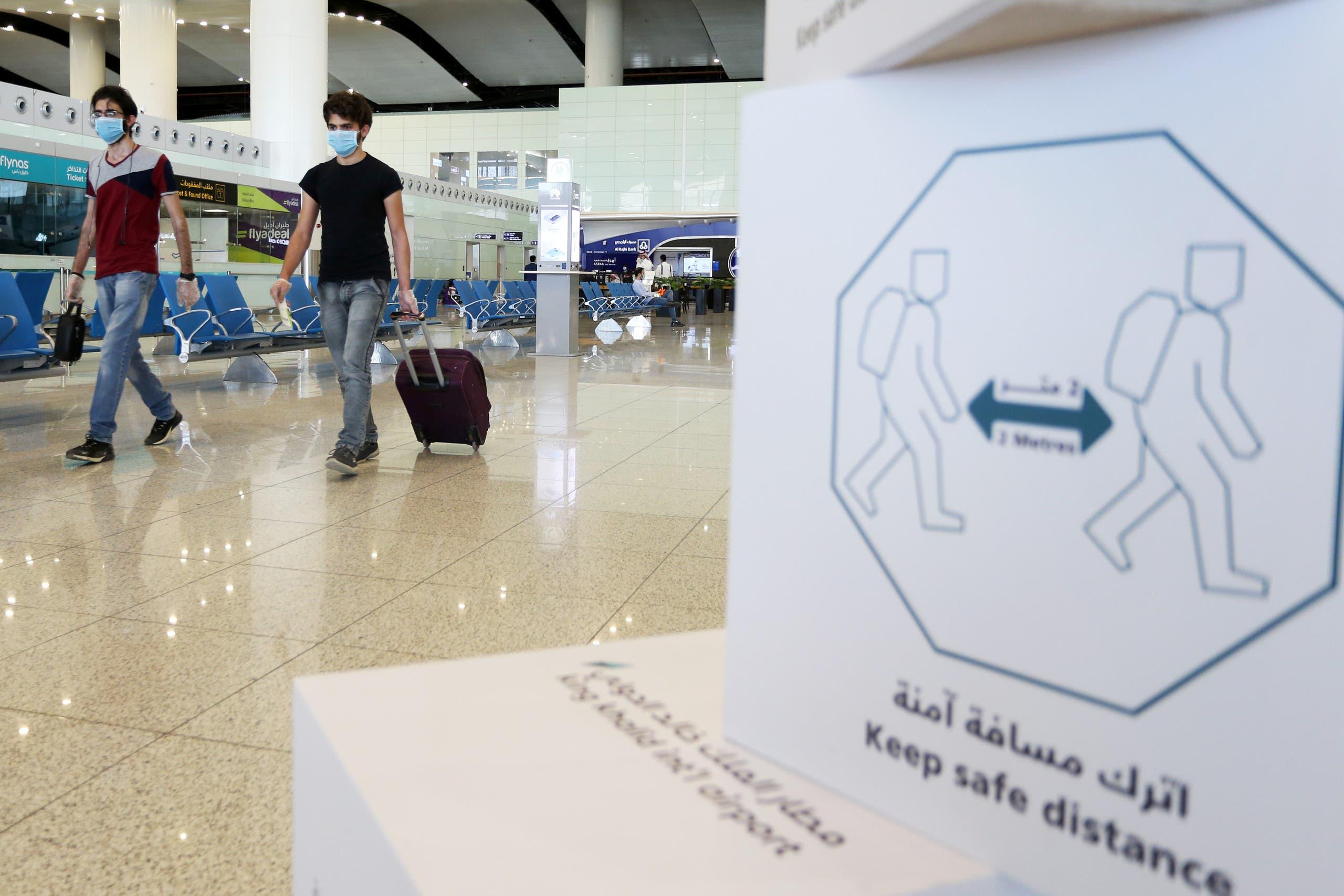 Travelers wearing protective face masks walk at Riyadh International Airport. (File photo: Reuters)