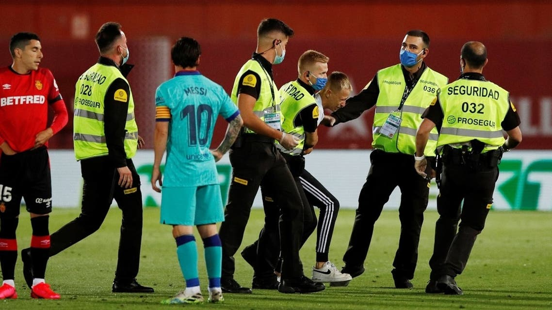 A pitch invader is apprehended by stewards, as play resumes behind closed doors following the outbreak of the coronavirus disease. (Reuters)