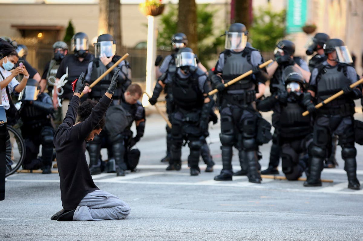 A file photo of a protester on his knees puts his hands up during a standoff with police in front of the Georgia State Capitol during a protest against the death of George Floyd, in Atlanta, Georgia, US. (File photo: Reuters)