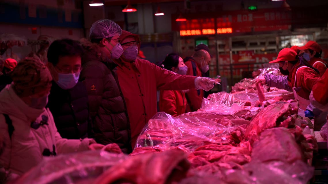 Customers wearing face masks buy pork meat at the Xinfadi wholesale market, as the country is hit by an outbreak of the novel coronavirus disease (COVID-19), in Beijing. (Reuters)