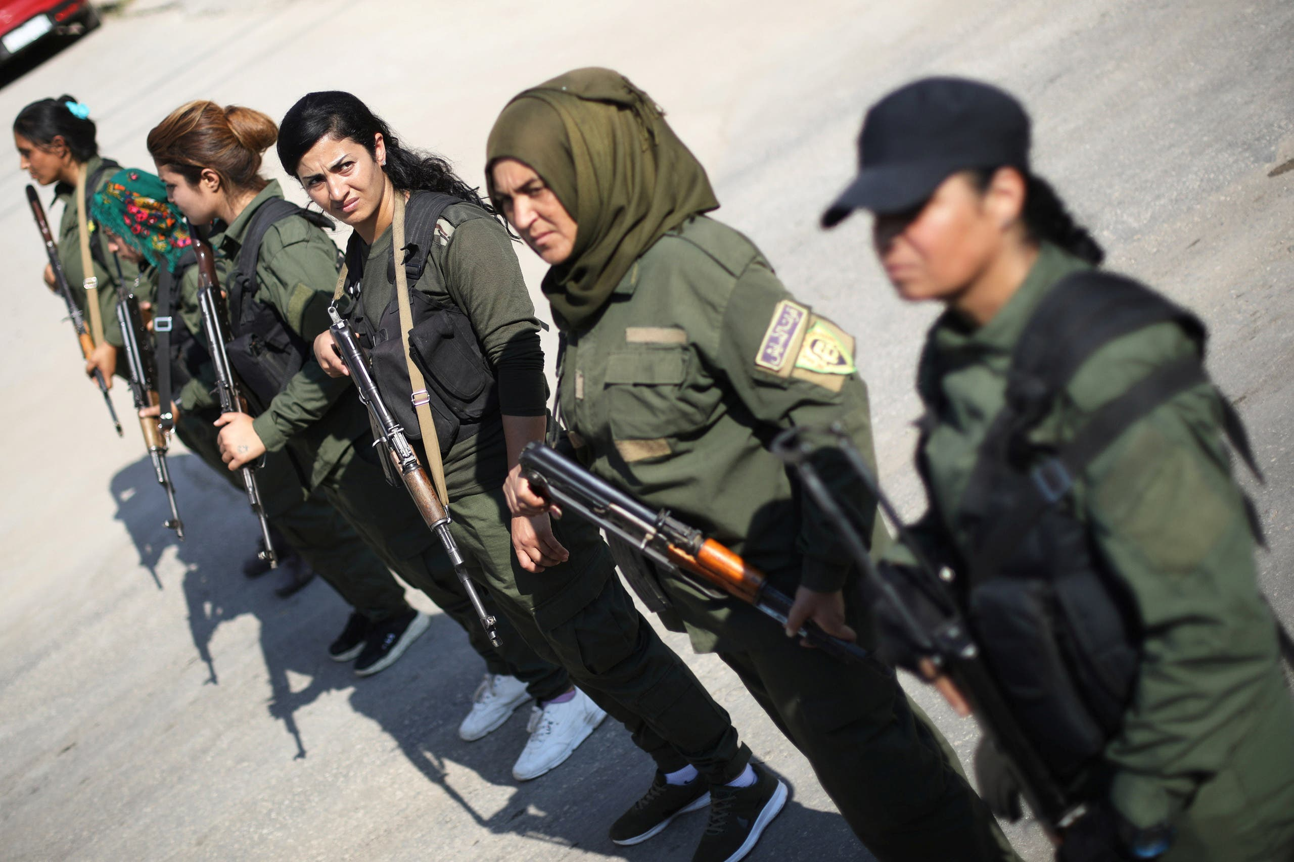 Kurdish policewomen stand guard as Kurdish and Arab protesters take part in a march against Turkish President and walk to the United Nations Headquarters in the town of Qamishli, Syria October 23, 2019. (Reuters)