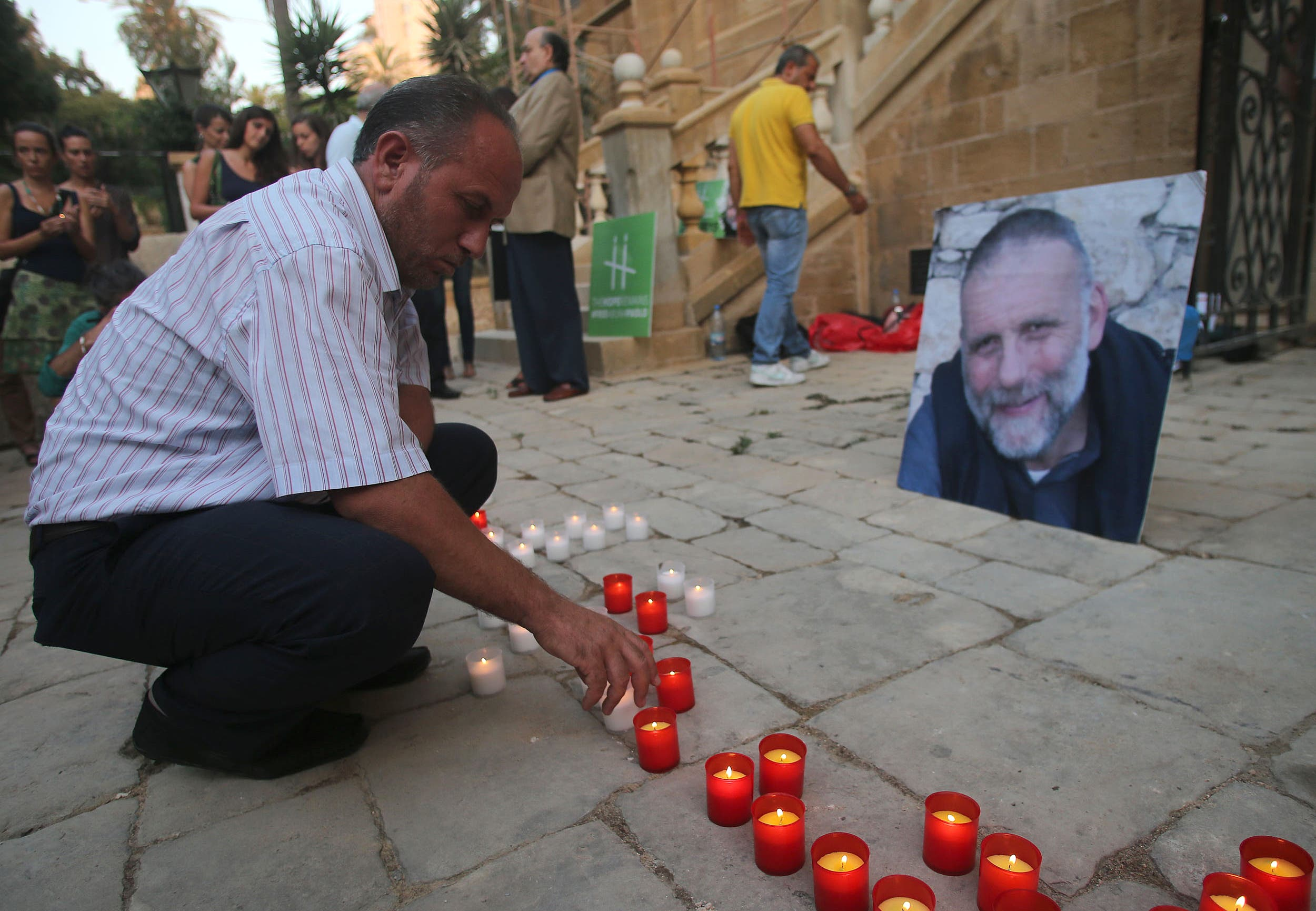 A man places a candle during a vigil in solidarity with Italian Jesuit priest Father Paolo Dall'Oglio on July 29, 2015 in Beirut. (AFP)