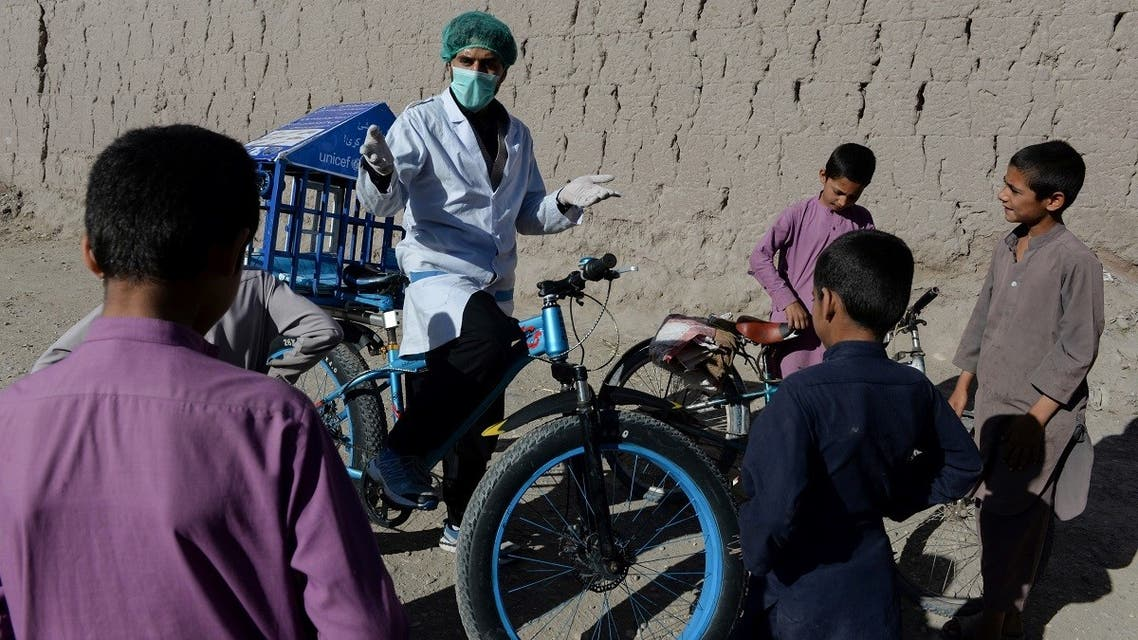 In this photo taken on May 19, 2020, 27-year-old Afghan cyclist Idrees Syawash (C) talks to children during an awareness campaign on coronavirus in the Surkh Rod district of Nangarhar province. (AFP)