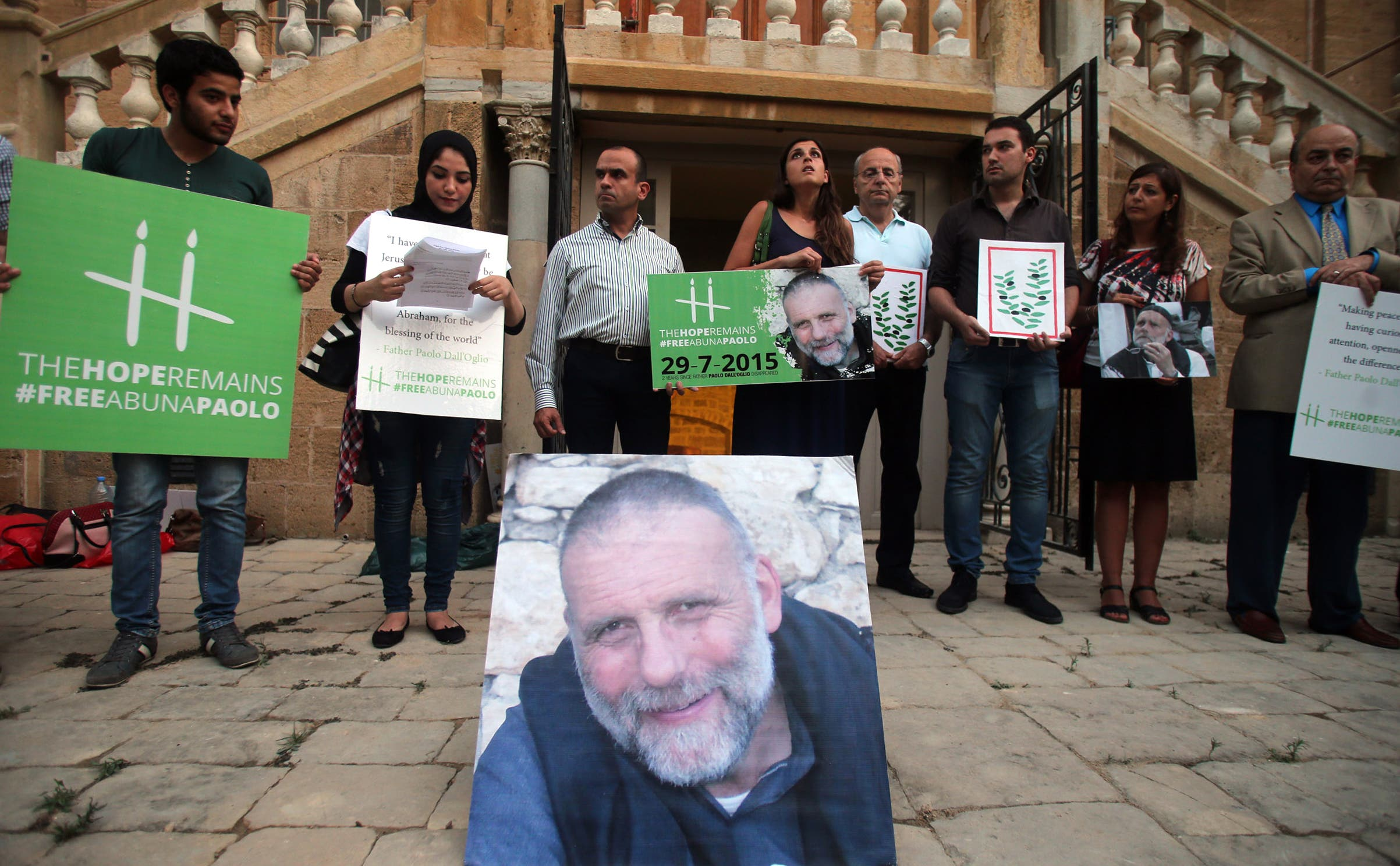 People hold placards during a vigil in solidarity with Italian Jesuit priest Father Paolo Dall'Oglio on July 29, 2015 in Beirut. (AFP)