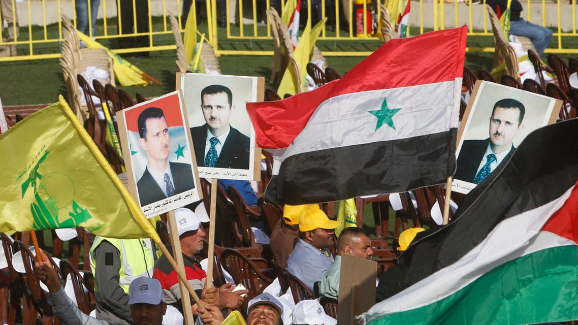 Supporters of Lebanon's Hezbollah leader Sayyed Hassan Nasrallah carry flags and pictures of Syria's President Bashar al-Assad during a rally marking al-Quds Day, (Jerusalem Day) in Maroun Al-Ras village, near the border with Israel, southern Lebanon June 8, 2018. (Reuters)