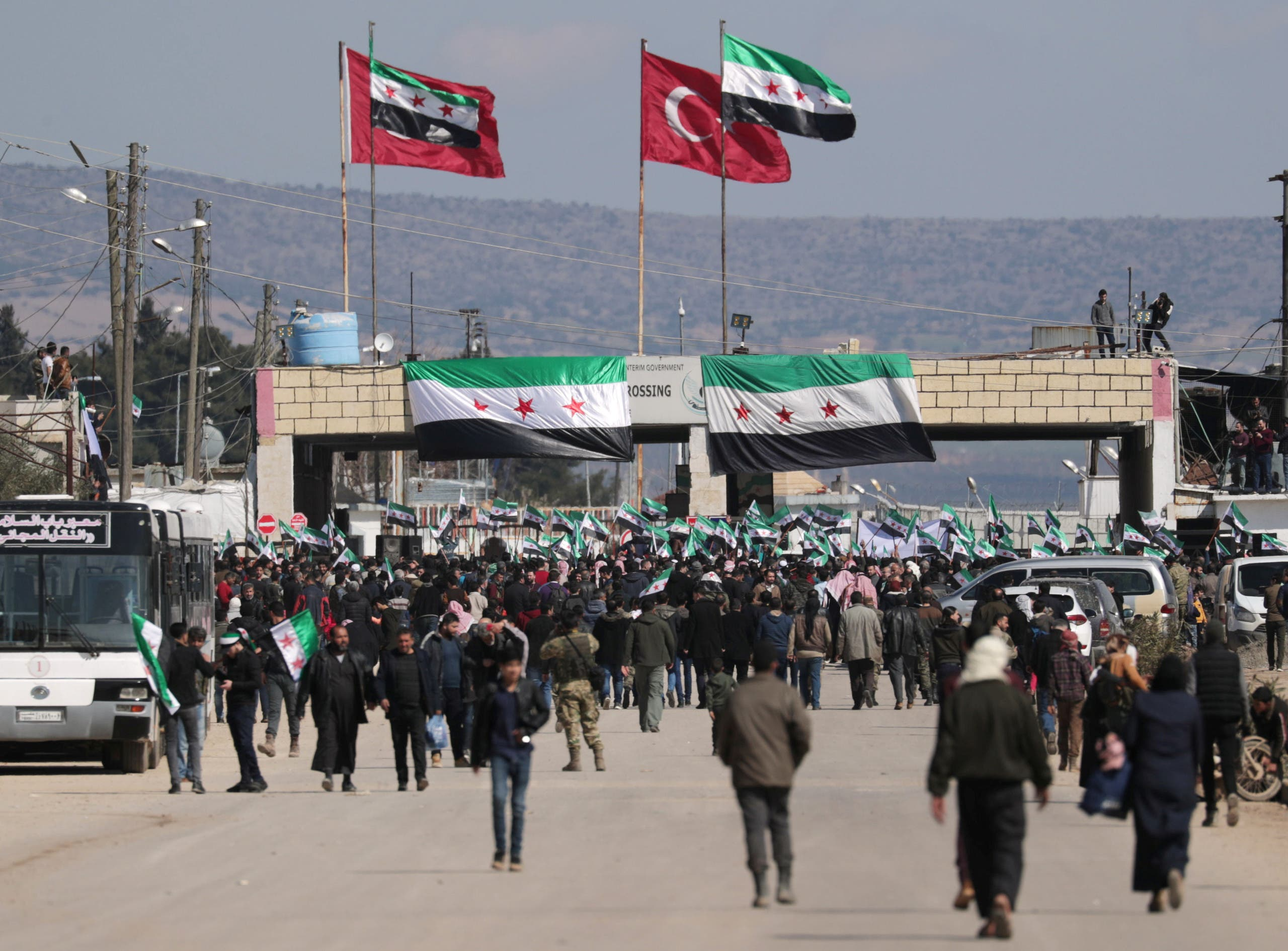 Internally displaced Syrians hold Syrian opposition flags during a protest in support of the Turkish army and Turkey backed Syrian rebels at the Bab el-Salam border crossing between the Syrian town of Azaz and the Turkish town of Kilis, in Syria, February 25, 2020. (Reuters)