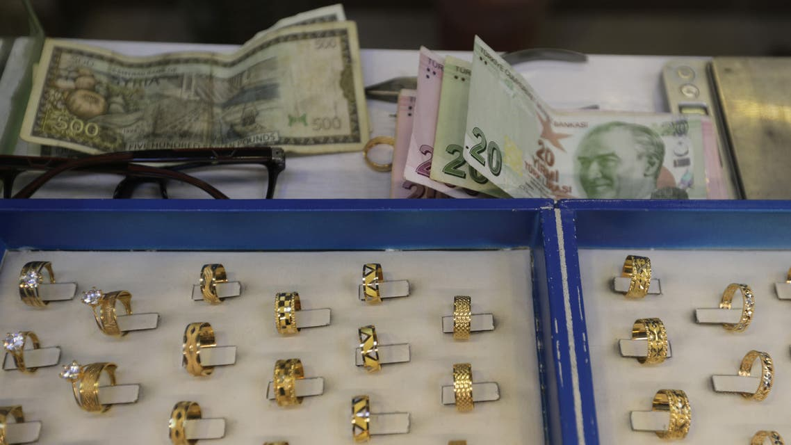 Turkish lira banknotes and Syrian pounds are pictured near gold rings for sale at a jewellery shop in Azaz, Syria February 3, 2020. Picture taken February 3, 2020. (Reuters)