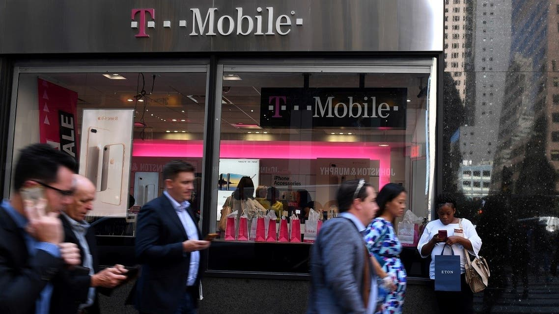 Pedestrians use their smart phones as they pass a T-Mobile retail store in Manhattan, New York, U.S., September 22, 2017. (Reuters)