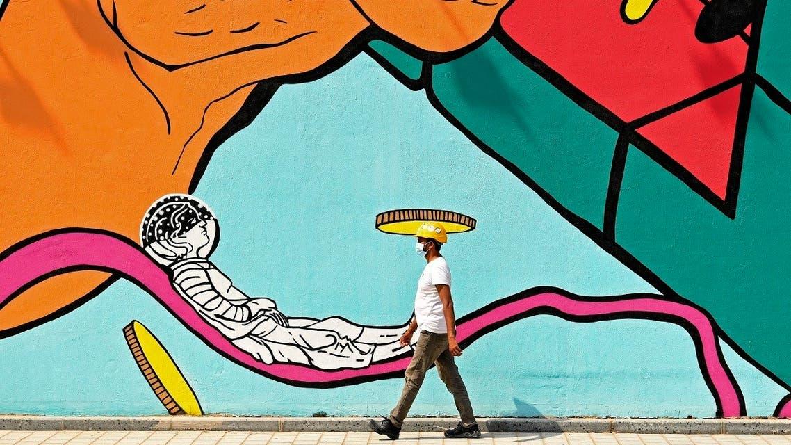A worker wearing a hard hat walks past a mural in Dubai on June 3, 2020. (AFP)