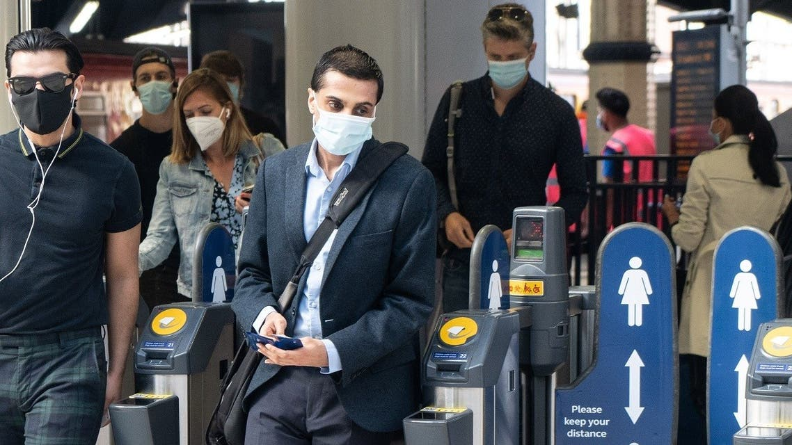 Commuters wearing face masks walk through the ticket barriers at Waterloo Station in London on June 15, 2020 after new rules make wearing face coverings on public transport compulsory while the UK further eases its coronavirus lockdown. (AFP)
