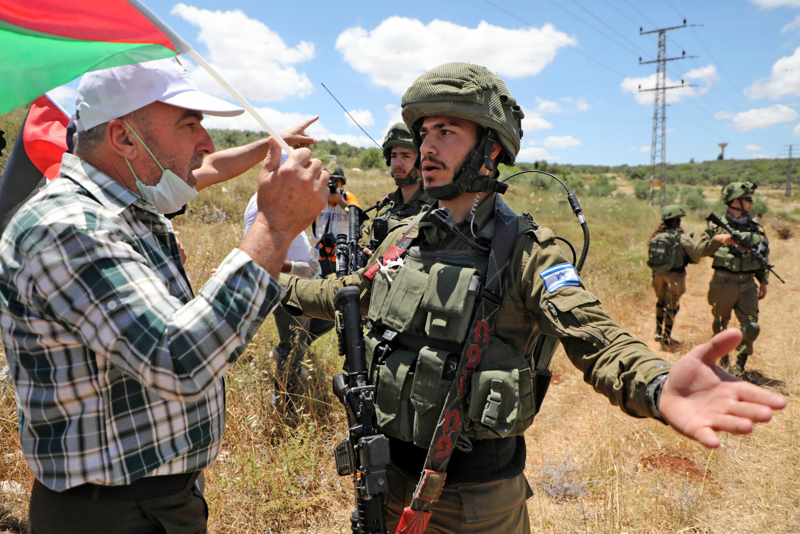 Palestinian protesters from the village of Haris in the occupied West Bank argue with Israeli soldiers, on May 29, 2020, during a protest against the expropriation of Palestinian land in favor of the Israeli settlement of Revava. (AFP)