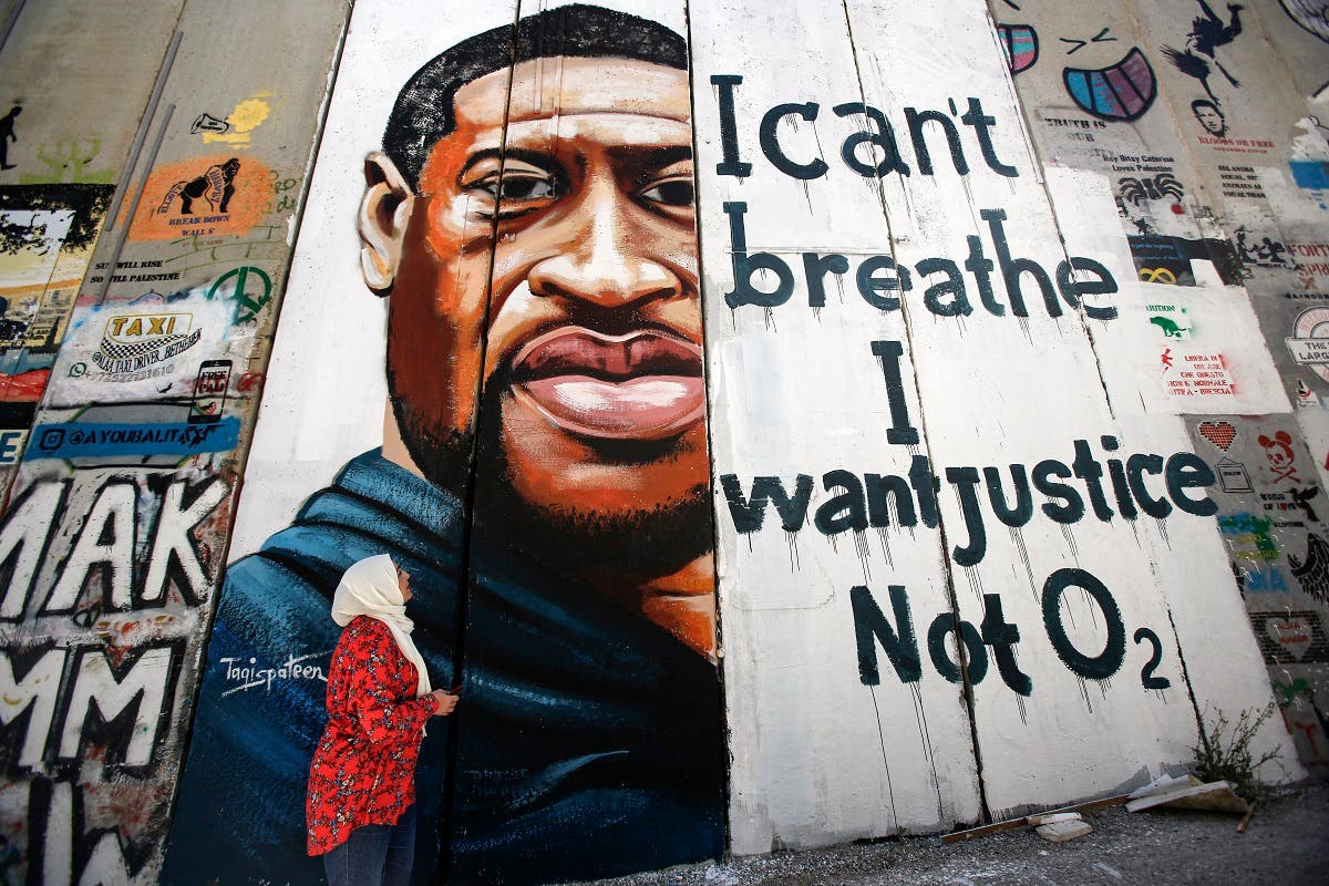 A woman looks at a mural showing the face of George Floyd painted on a section of Israel's controversial separation barrier in the city of Bethlehem in the occupied West Bank on June 10, 2020. (AFP)