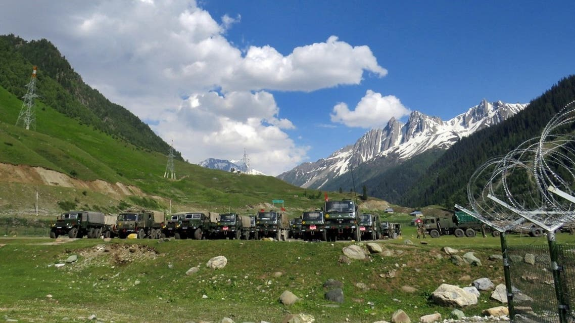 Indian army soldiers walk past their parked trucks at a makeshift transit camp before heading to Ladakh, near Baltal, southeast of Srinagar, June 16, 2020. (Reuters)